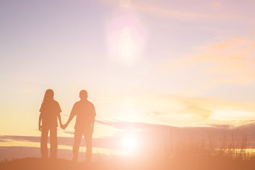 Silhouette of a female and male holding hands at sunset