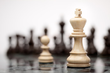 Brave soldier / Leadership and bravery concept; white wooden single pawn staying against a white king on chessboard.