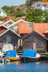 Old boat houses with boats in harbor