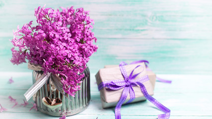 Aromatic  lilac flowers in vase and boxes with gifts on turquois