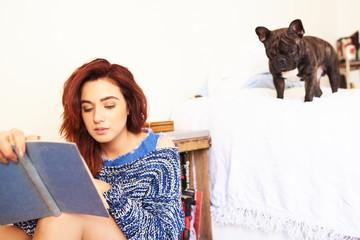 girl reading book in bedroom.Black bulldog on bed