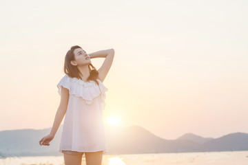 beautiful young woman standing look at the sky nearing seaside i