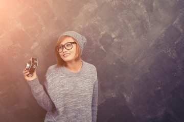 Smiling hipster woman wearing glasses holding a retro camera aga