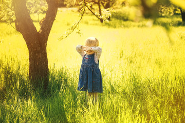Little girl covered her face with hands. Child playing hide and seek game in sunny garden or backyard on spring sunny day. Small baby standing near huge tree in park.