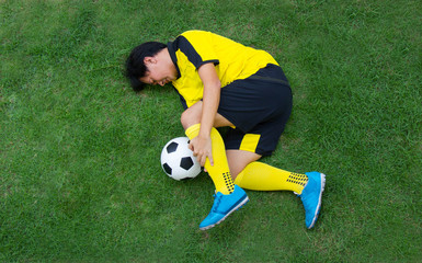 Football player in Yellow lying injured on the pitch.