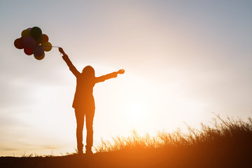 silhouette of Young  woman holding colorful of balloons with sun
