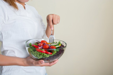 hands of beautiful woman holding big bowl of fresh veggie salad