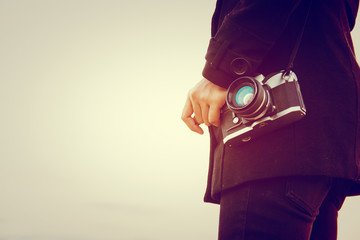 Young woman wearing black coat standing carry retro camera