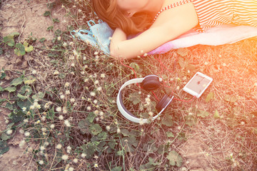 top view of young woman lying nearing headphone in the flower fi