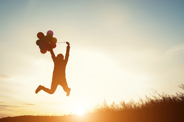 young woman with balloons jumping outdoor
