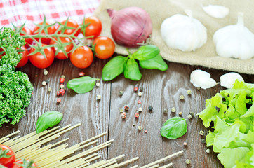 Tomatoes, spaghetti, onion and garlic on wooden table
