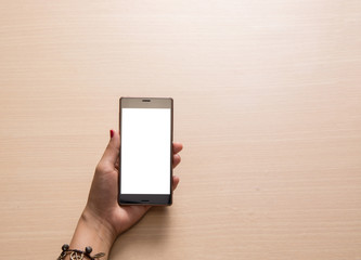 Smartphone in hand, close up on the wooden background