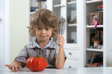 Unhappy child sitting at the table looking at tomato. Bad eating habits, nutrition and healthy eating concept.