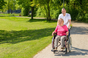 Elderly woman seated in wheel chair by husband