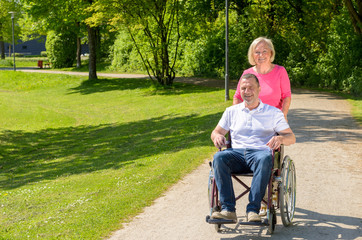 Man seated in wheel chair while wife pushes