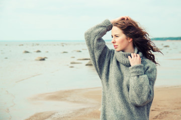 Attractive woman wearing a warm cardigan at the cold beach