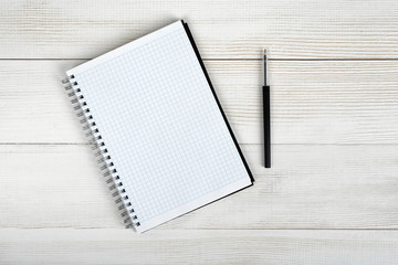 Top view of open empty notebook and black pen.