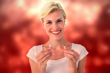 Composite image of attractive blonde woman snapping cigarette an