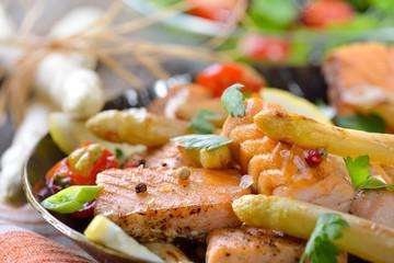 Gebratener bayerischer Spargel mit Lachsstreifen in der Eisenpfanne mit Rucola-Beilagensalat serviert - Roasted  white asparagus with fried salmon served in an iron frying pan with a rocket side salad