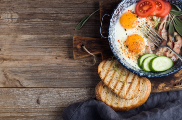Breakfast set. Pan of fried eggs with bacon, fresh tomato, cucumber, sage and bread on rustic serving board over wooden background