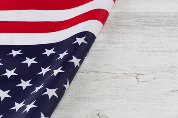 Amerian flag folded diagonnaly on white rustic wooden table. Horizontal image with copy space