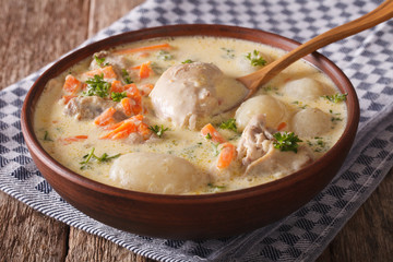 Creamy soup with chicken and vegetables close up in a bowl. horizontal