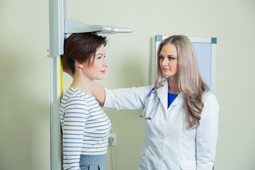 Doctor measures growth woman in medical office