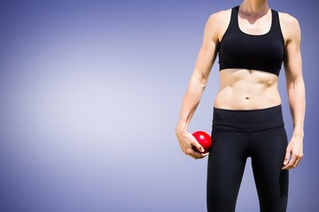 Composite image of sporty woman holding a red ball