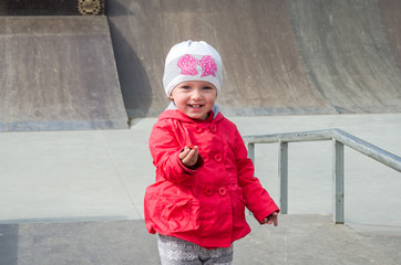 Young beautiful girl baby in a red jacket and white hat playing on the playground in the skate park, inhaling the aroma of yellow dandelion flower, smiling and having fun