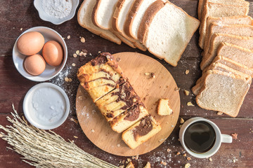 Love of Coffee cup and chocolate marble cake on cutting board with bread and ingredient in kitchen