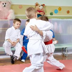 Children look sparring athletes in judo