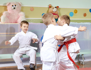 Two boys are trained judo sparring before other athletes