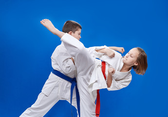 With red and blue belt the children are beating  karate blows
