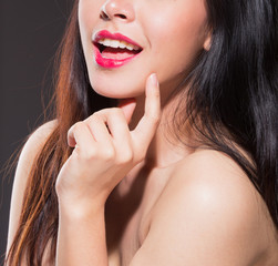 Portrait of beautiful young woman with naked shoulders,on black background,Focus on mouth.