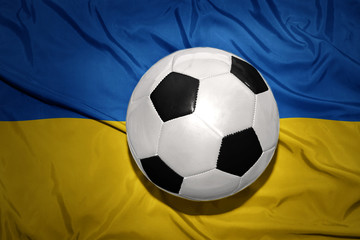 black and white football ball on the national flag of ukraine