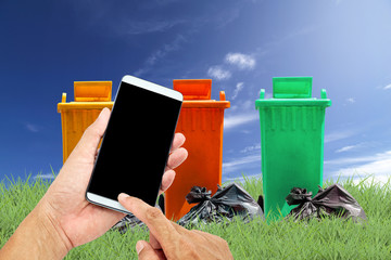 man using mobile smart phone control with recycle bins and bag g