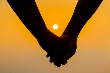 Romantic couple with clasped hands backlit by a bright evening sun in a closeup conceptual image of love