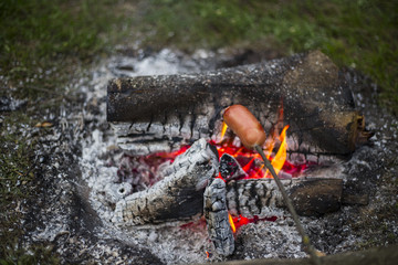 Cooking sausages over a fire.