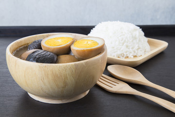 Five spice pork and egg stew with wooden kitchenware on black ba