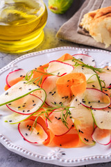 Vegetarian salad of carrot, cucumber and radish.