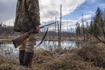 Autocollant pour porte Chasse Hunter standing in the swamp in the forest and holding in his hand an old hunting rifle