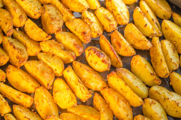 Golden baked sliced potatoes, laid out in rows on the baking sheet