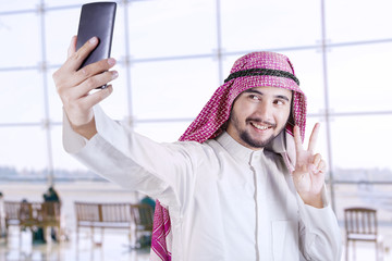 Arabic tourist taking selfie in the airport
