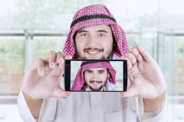 Arabic worker takes selfie in the office lobby
