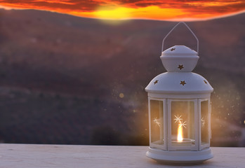 Lantern with candle and light, with sundown in the mountains on background. Ramadan concept