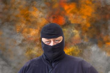 Mann mit Sturmhaube vor einem Hintergrund aus Rauch und Flammen - fototapety na wymiar