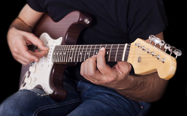 Man playing electric guitar on black background