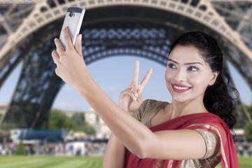 Indian woman takes selfie at Eiffel Tower