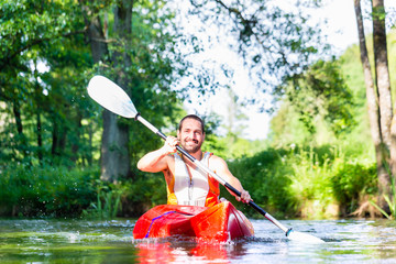 Man paddling with canoe on forest river