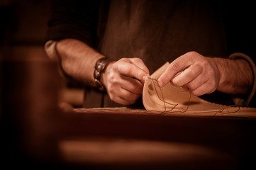 Leather goods craftsman at work in his workshop